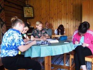 Leiriläiset vierasmajalla oppitunnilla, jonka aiheena on rukous. Kristinoppikoulun tai –leirin oppitunneilla tutustutaan sakramentteihin, jumalanpalveluselämään ja kirkollisiin tapoihin.
